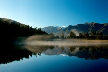 Sun catches early morning mist at Lake Matheson