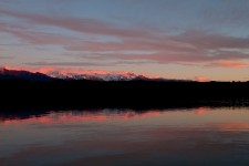 Sunset rays turn snow pink on Southern Alps at Okarito lagoon
