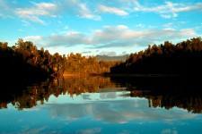 Rippled reflections of the native bush at Okarito Lagoon